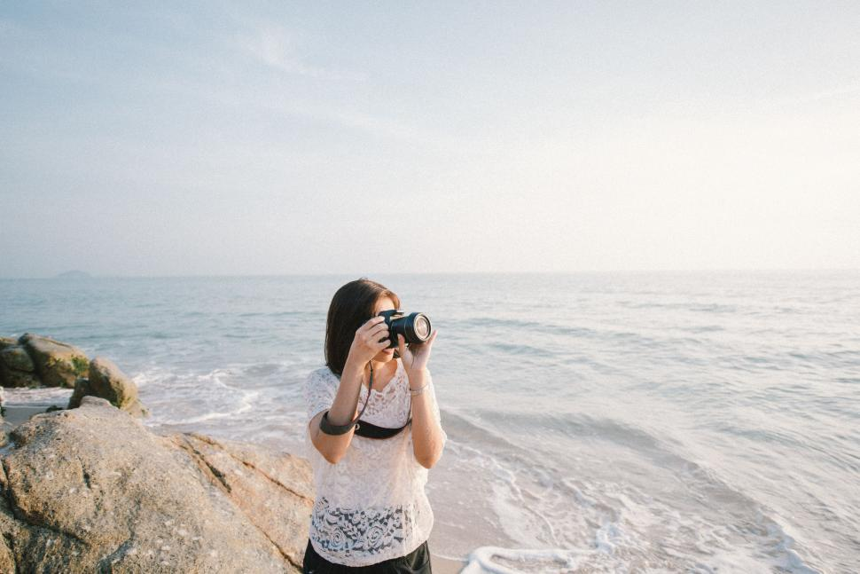Download Free Stock Photo of Woman Photographer at Ocean Rock