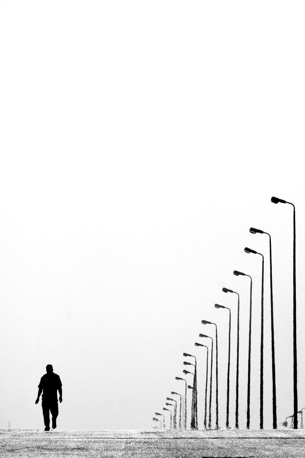 Download Free Stock HD Photo of Silhouette of walking man besides row of lamp posts  Online