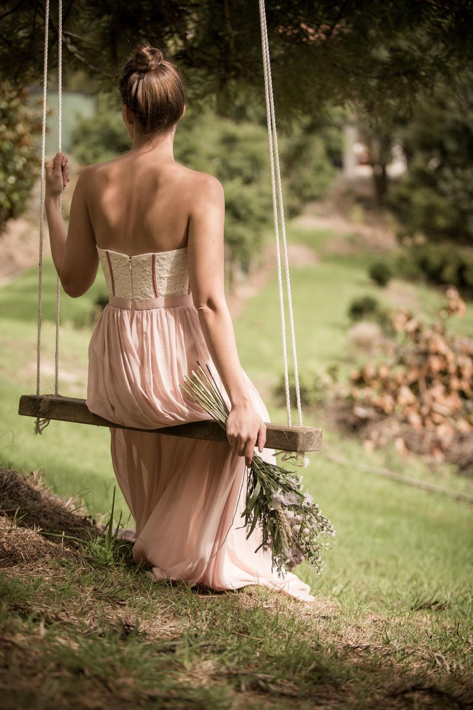 Download Free Stock Photo of Woman on swing holding flower bouquet