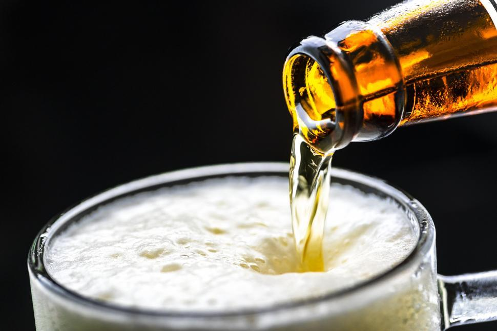 Download Free Stock HD Photo of Beer frothing while being poured into a pint mug Online