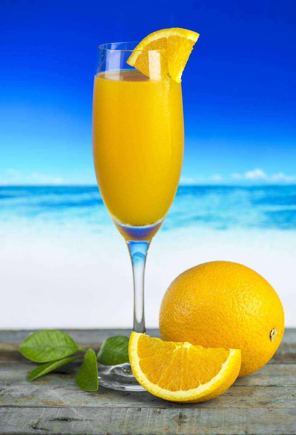 Download Free Stock HD Photo of Close up of orange juice in a glass, beach scene Online