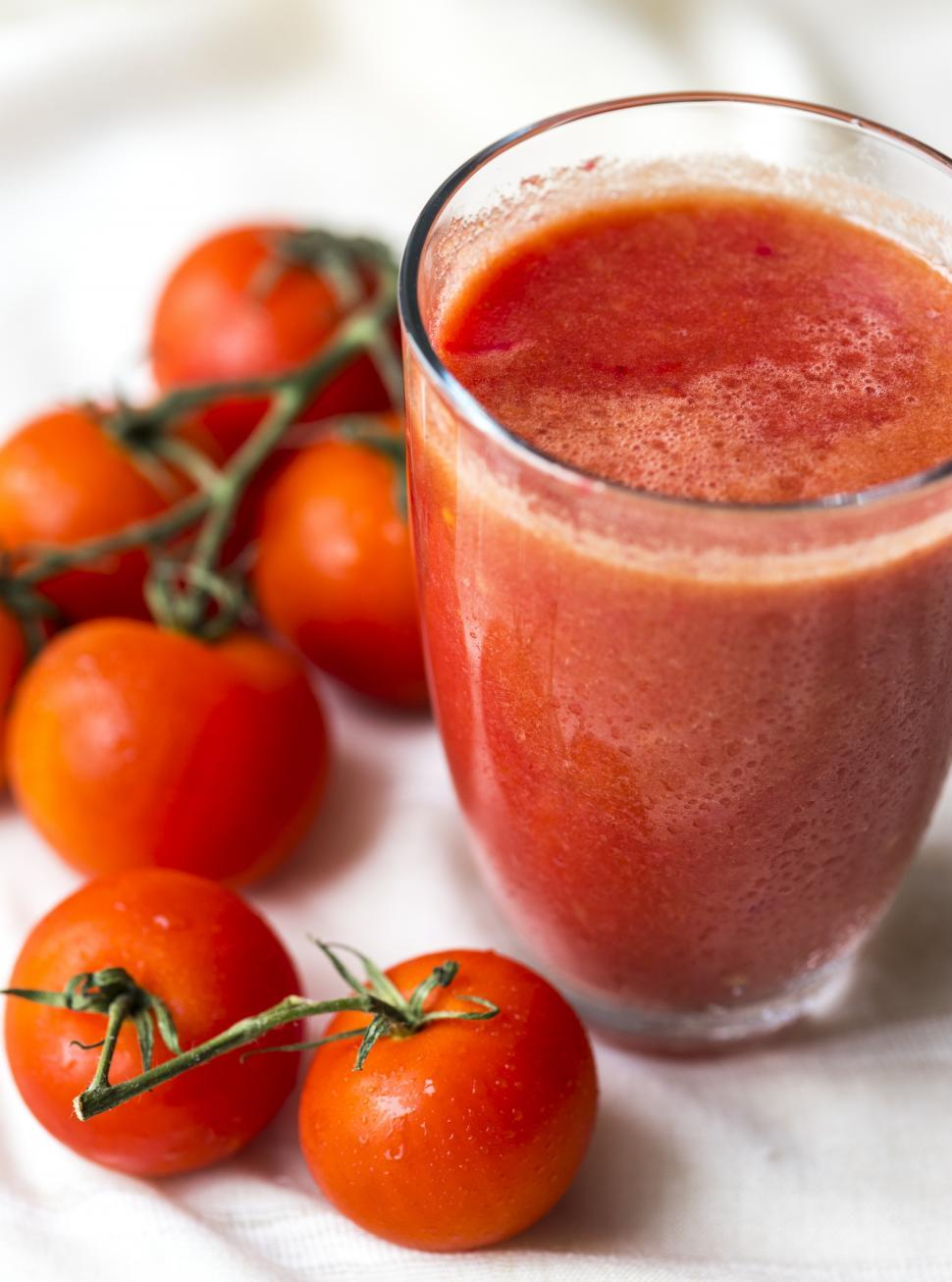 Download Free Stock Photo of Close up of a glass of tomato juice with whole tomatoes