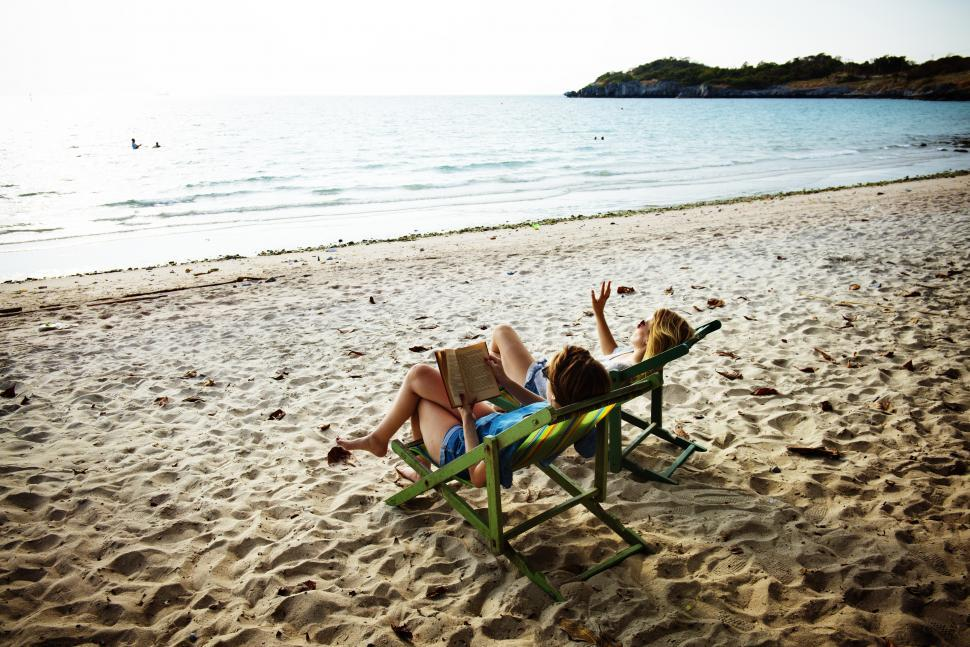 Download Free Stock Photo of A young woman reading book with a friend on the beach