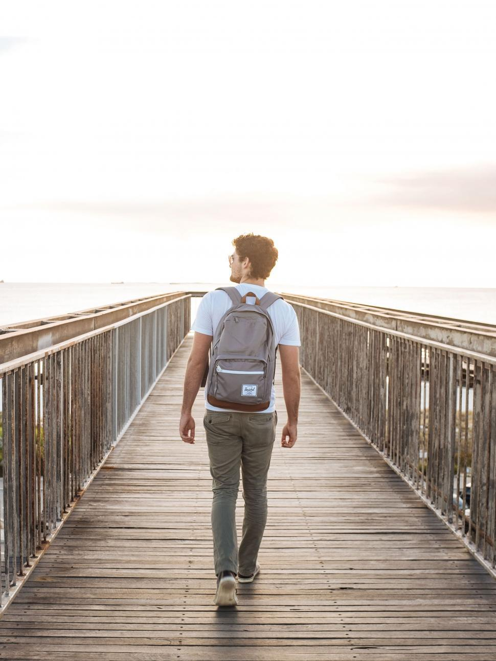 Download Free Stock Photo of Back side view of man walking on pier