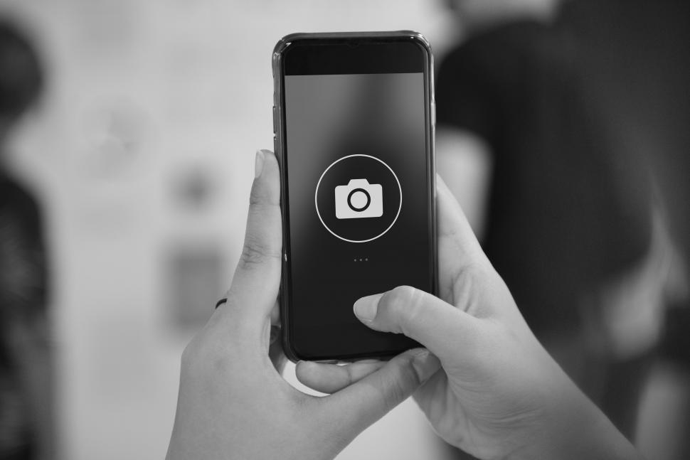 Download Free Stock Photo of Close up of a smart phone in a persons hands with camera icon