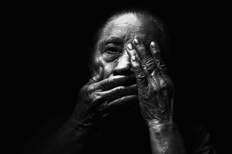 Download Free Stock Photo of Dark View of Old Woman with hands on face