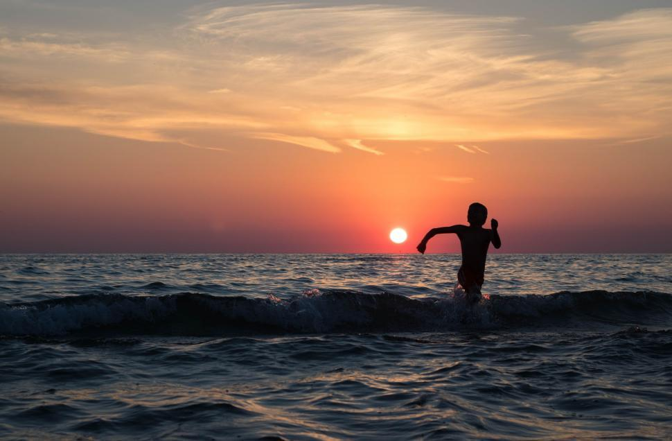 Download Free Stock Photo of Boy Playing in Ocean during Sunset