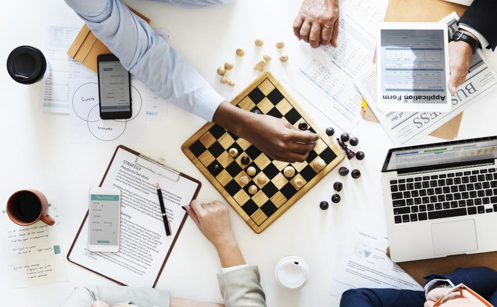 Download Free Stock Photo of Overhead view of people playing chess surrounded by technology