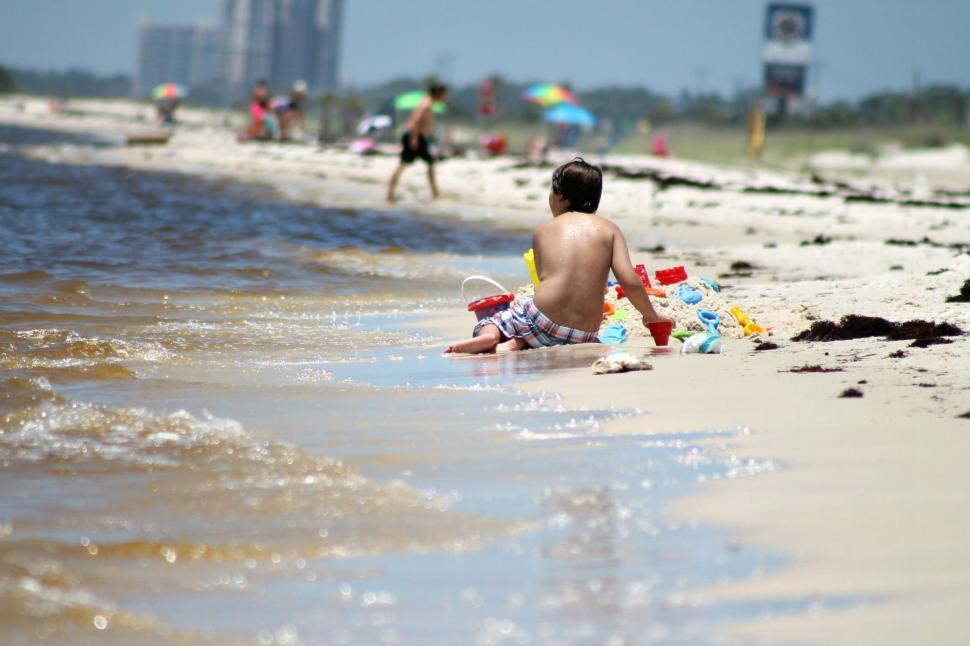 Download Free Stock Photo of Young Boy Playing With Beach Sand