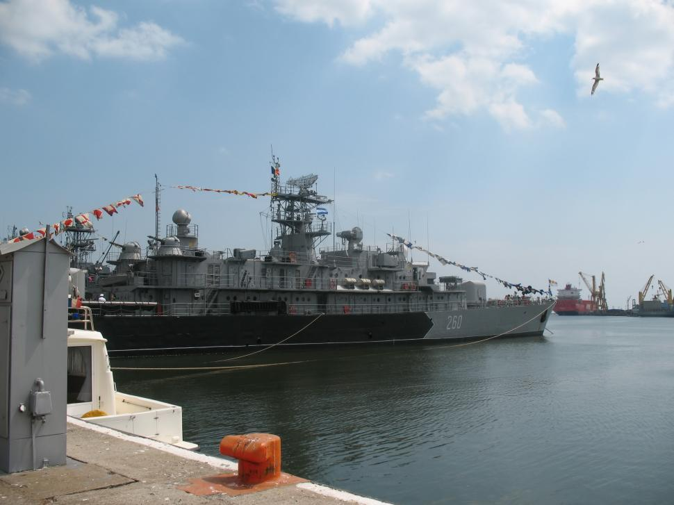 Download Free Stock HD Photo of A war ship at the dock open ocean in the background Online