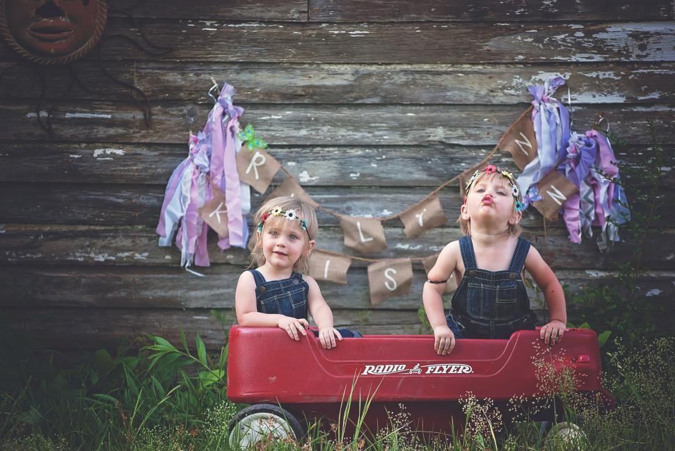 Download Free Stock Photo of Cute Little Twin Sisters Sitting in Wagon Toy Against Wooden Plank Wall