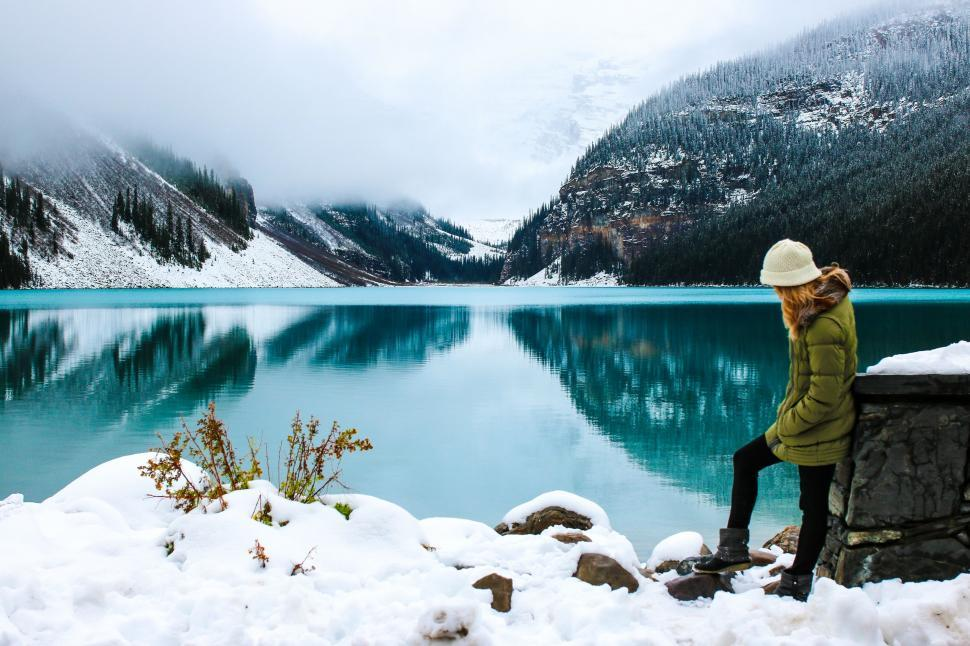 Download Free Stock Photo of Woman and Lake Louise With Snow Mountains During Foggy Winter Morning