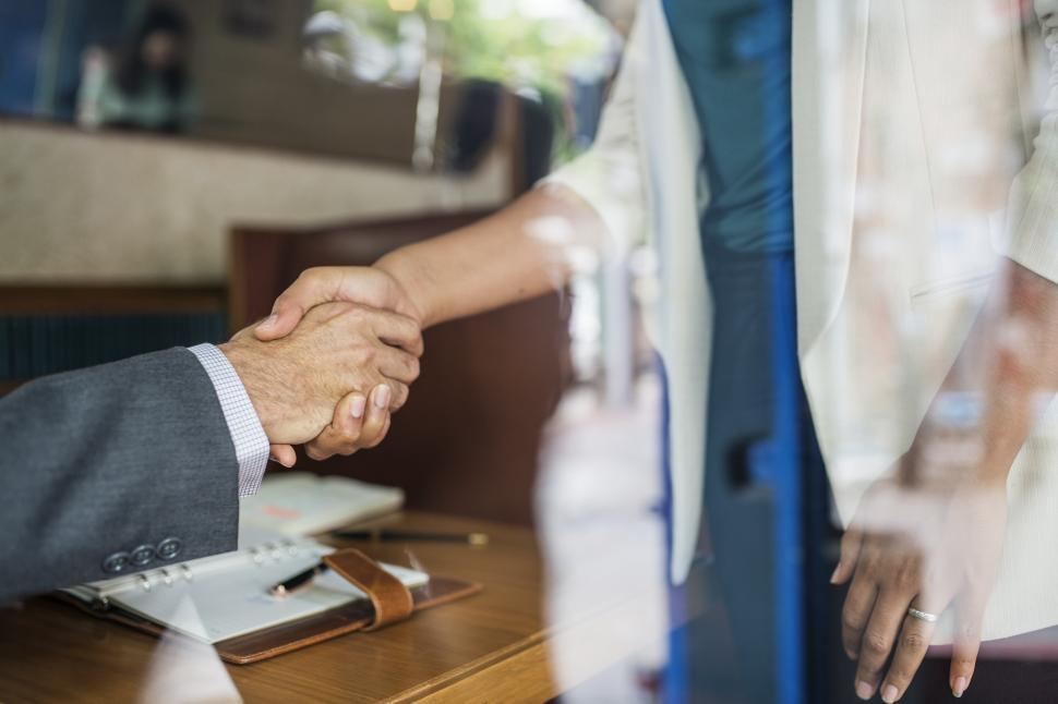 Download Free Stock Photo of Looking through a window at a handshake between two business people