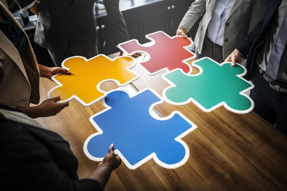 Download Free Stock HD Photo of A group of colleague joining big colorful jigsaw puzzle cutouts Online