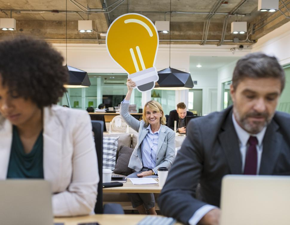 Download Free Stock Photo of A woman holding a lightbulb idea shaped cardboard cutout over her head