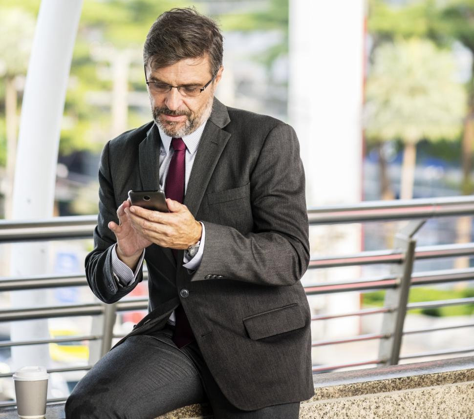 Download Free Stock Photo of A bearded businessman operating his mobile phone sitting on a railing