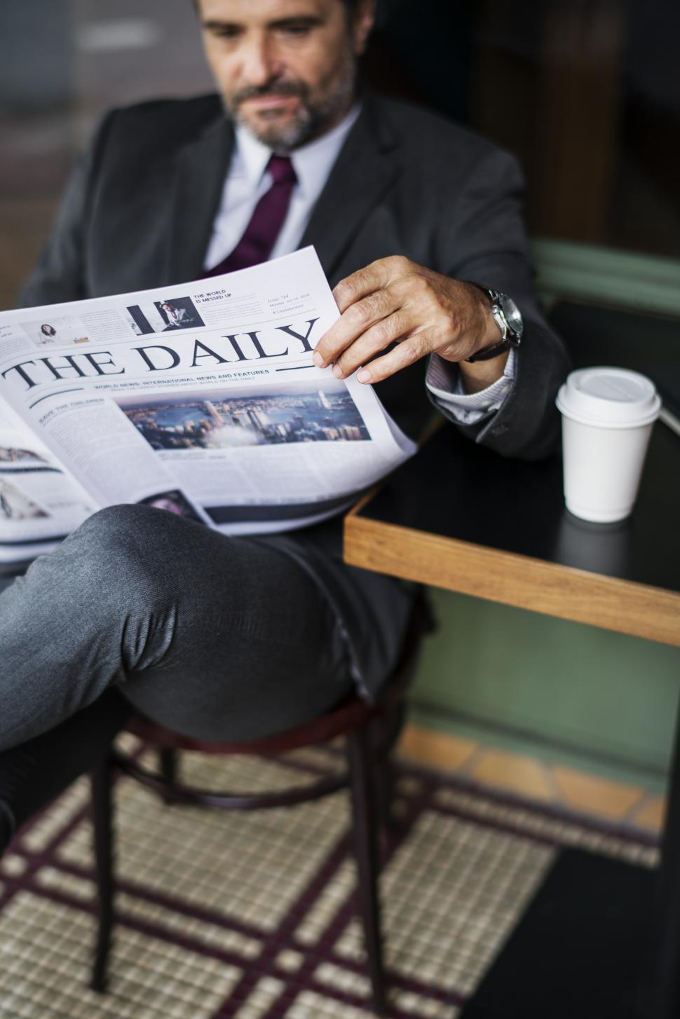 Download Free Stock Photo of A bearded businessman reading daily newspaper