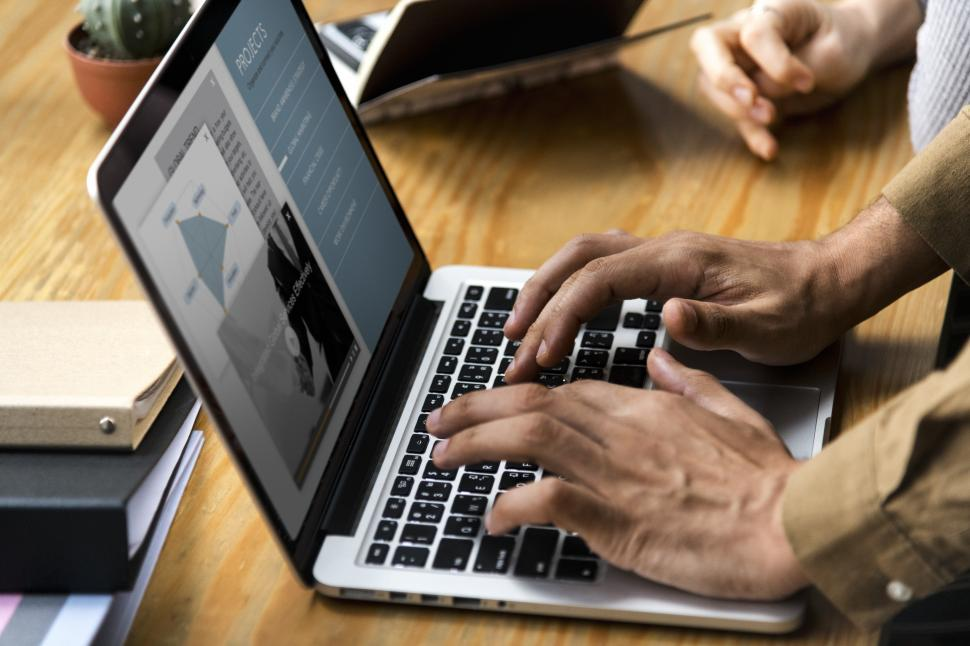 Download Free Stock Photo of Close up of a persons hands typing on a modern laptop