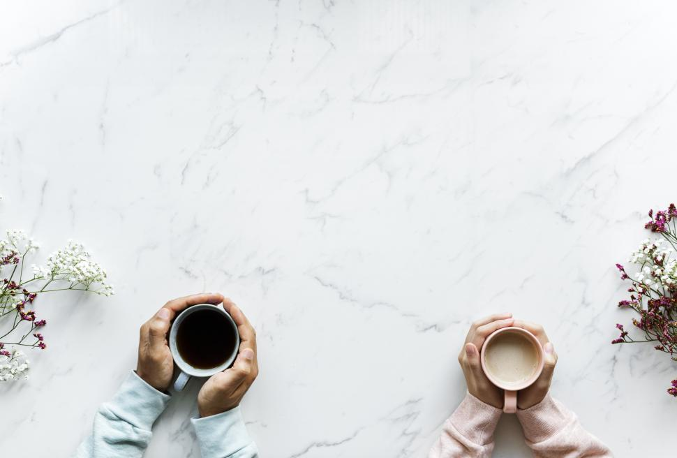 Download Free Stock Photo of Overhead view of two sets of hands holding coffee mugs in their palms