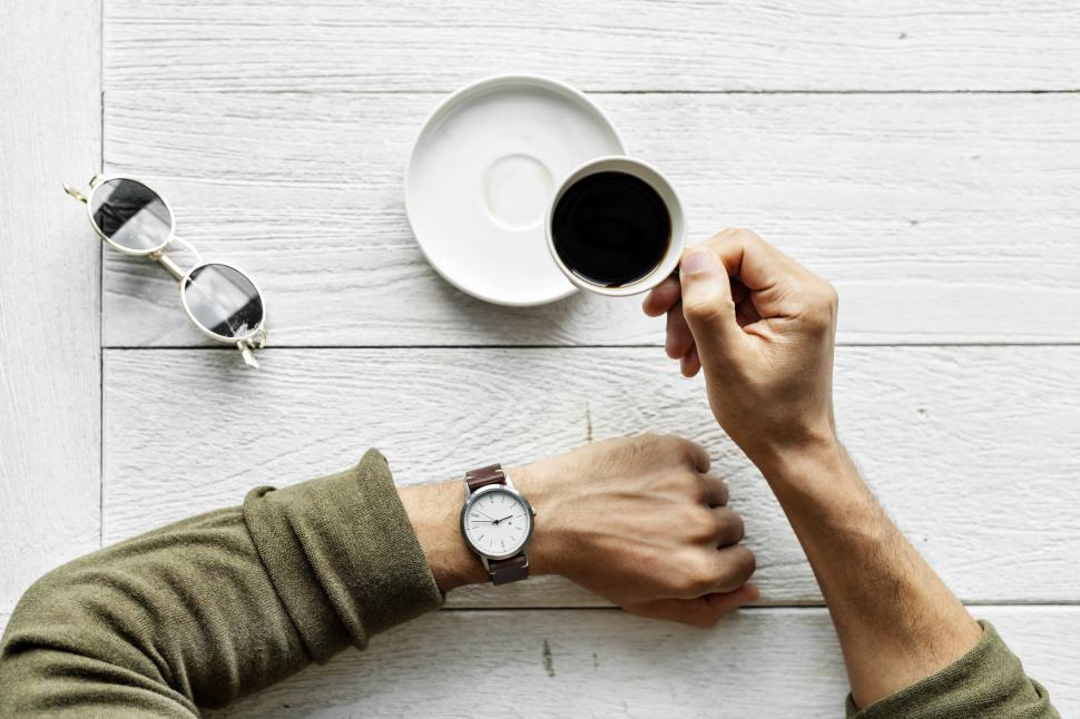 Download Free Stock HD Photo of Overhead view of a hand holding a cup of coffee, checking watch for time Online