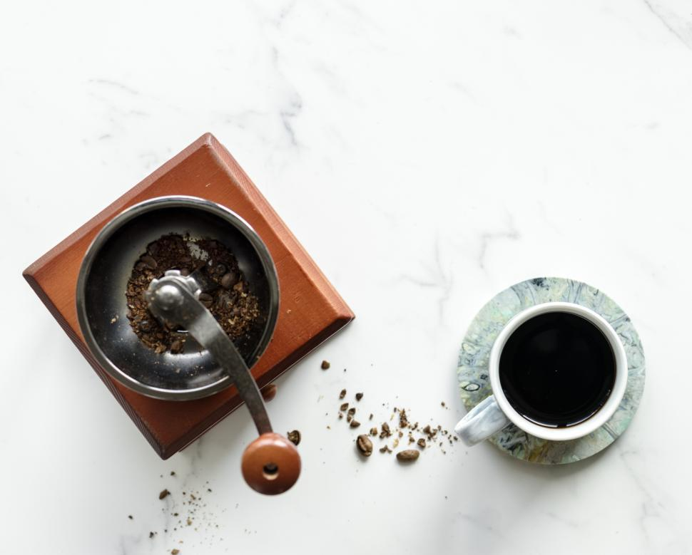 Download Free Stock HD Photo of Flat lay of a hand cranked coffee grinder and a cup of coffee Online