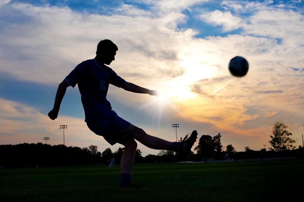 Download Free Stock Photo of Boy playing football in the sunset