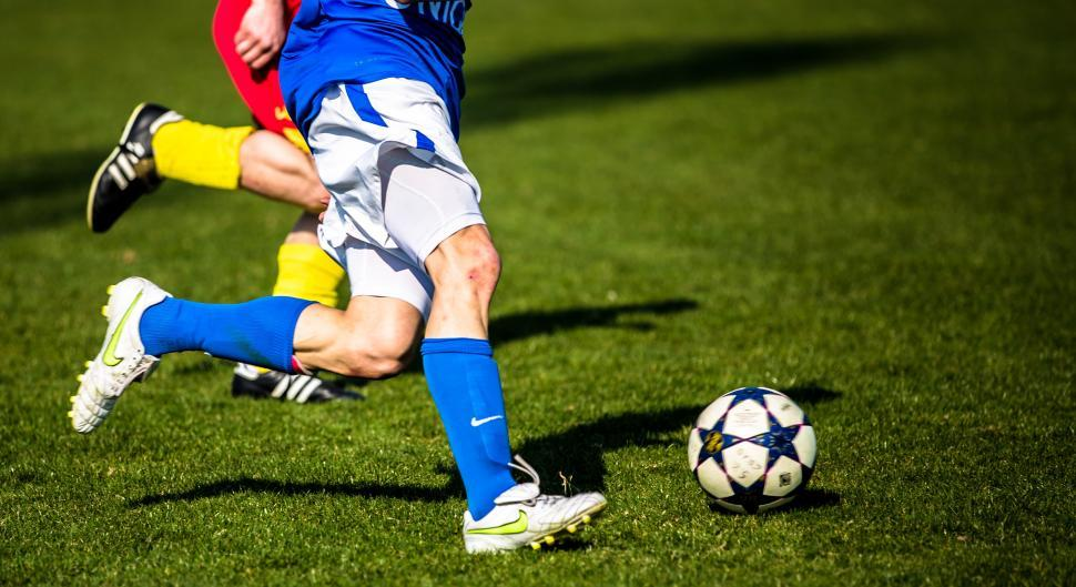 Download Free Stock Photo of Football Players running for the ball in a soccer game