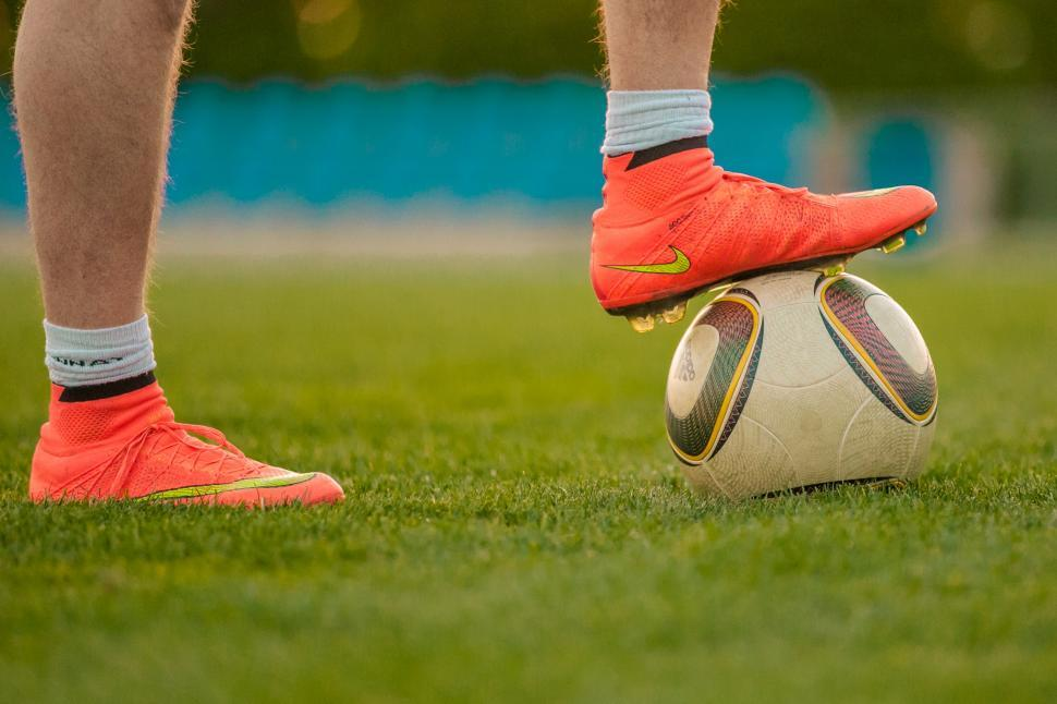 Download Free Stock Photo of Footballer with his foot on a football