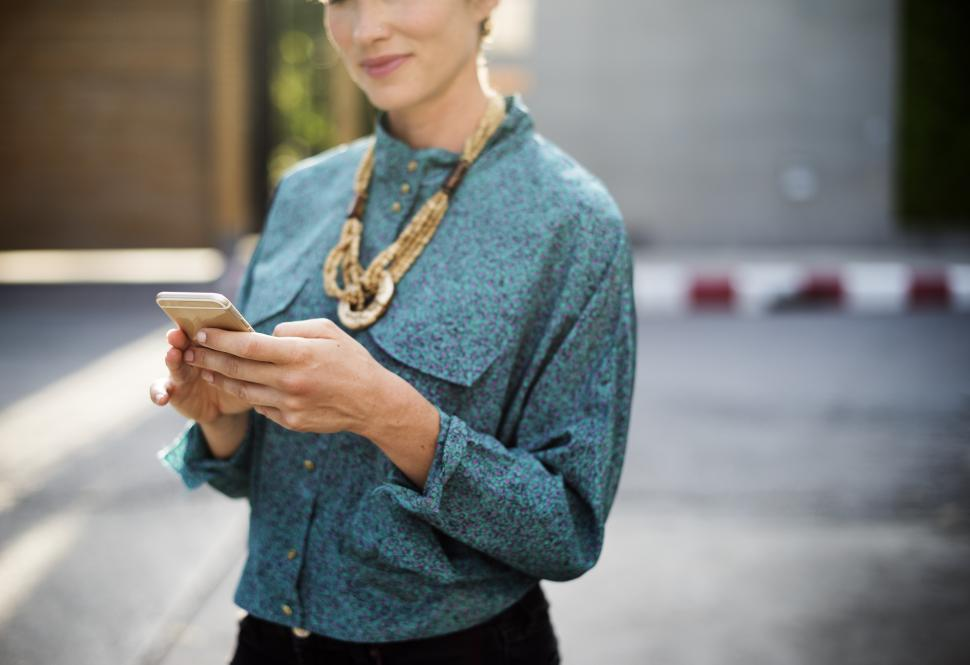 Download Free Stock HD Photo of A stylish young woman looking at her mobile phone Online