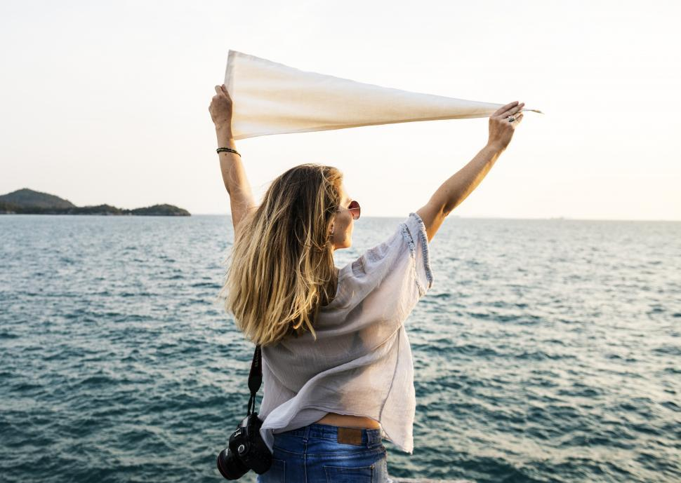 Download Free Stock HD Photo of A young woman holding white flag high at a seashore Online