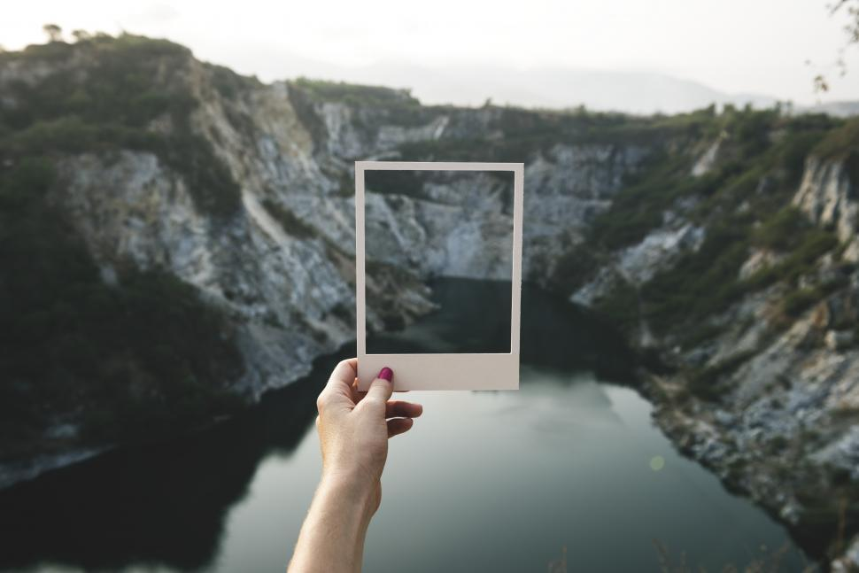 Download Free Stock Photo of Holding a photo frame shaped paper cut out in front of landscape