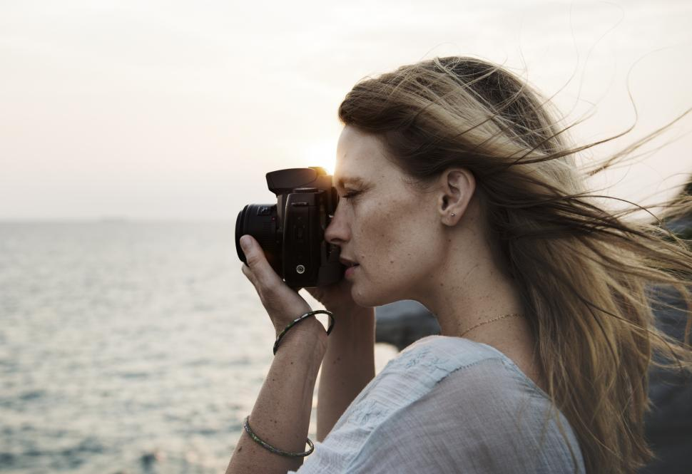 Download Free Stock Photo of Side view of a young woman taking photograph at sunset