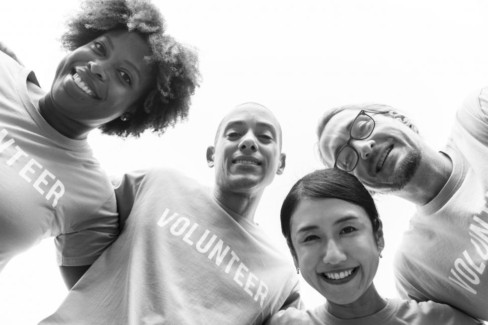 Download Free Stock HD Photo of Low angle view looking up at a volunteers  huddle in black and white Online