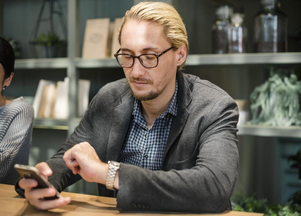 Download Free Stock HD Photo of A young Caucasian man checking time Online