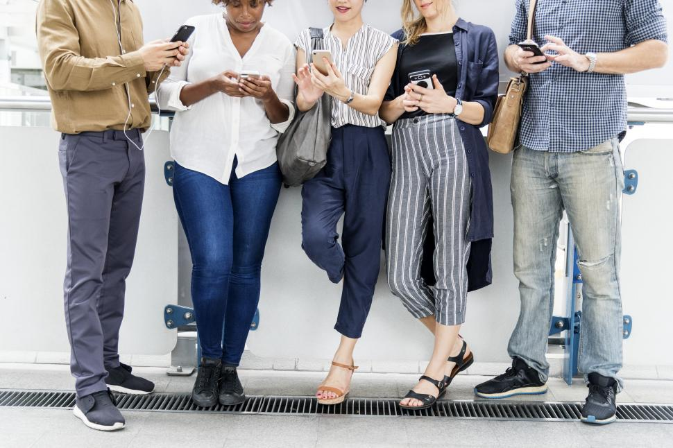 Download Free Stock Photo of Colleagues looking at their mobile phones, leaning on a wall