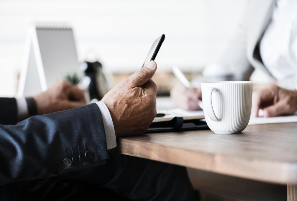 Download Free Stock Photo of Close up of person holding a mobile phone at a desk