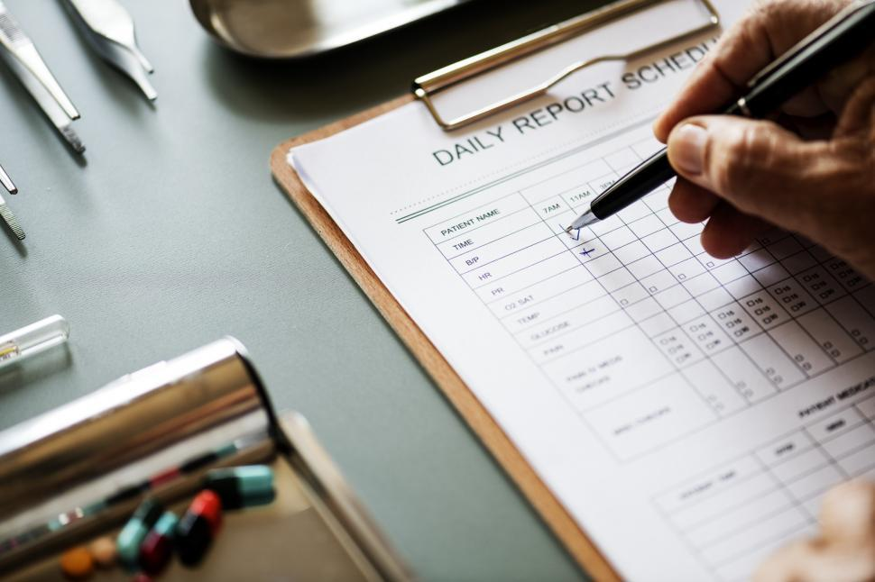 Download Free Stock HD Photo of Close up of a doctor hand checking schedule report Online