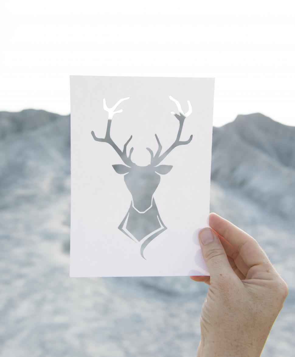 Download Free Stock Photo of A hand holding a stag shaped paper cut out white template