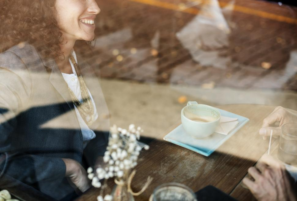 Download Free Stock Photo of A young woman at a cafe table seen through window reflections