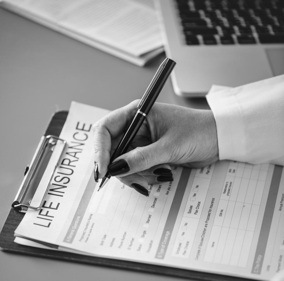 Download Free Stock Photo of Close up of a doctor s hand writing on the insurance questionnaire