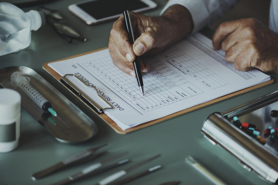 Download Free Stock HD Photo of Close up of a doctor s hand checking schedule Online