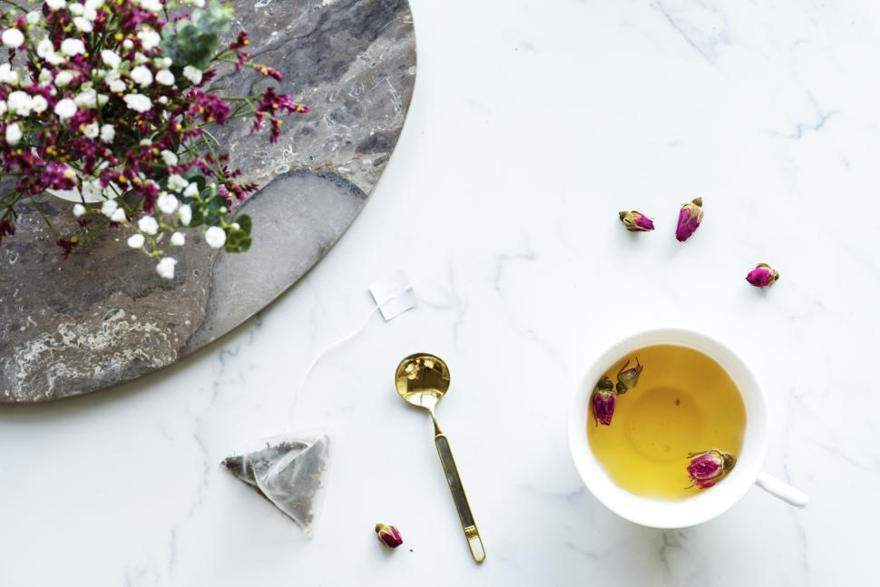 Download Free Stock HD Photo of Overhead view of a cup of herbal tea alongside flowers - white background Online