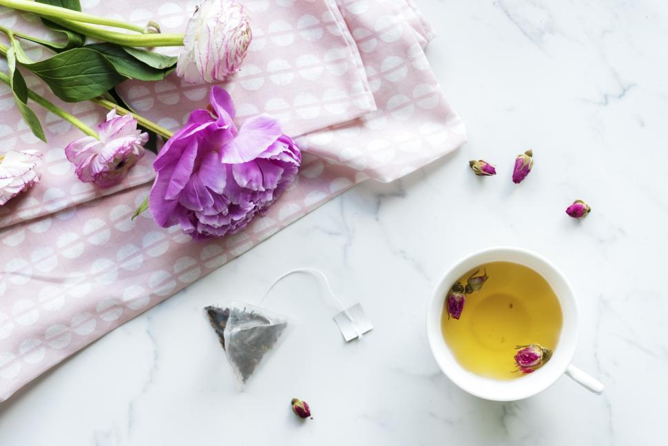 Download Free Stock HD Photo of Overhead view of a cup of herbal tea alongside purple flowers Online