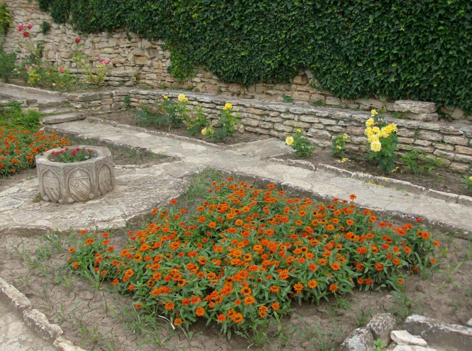 Download Free Stock Photo of Small garden full with flowers and stone alleys