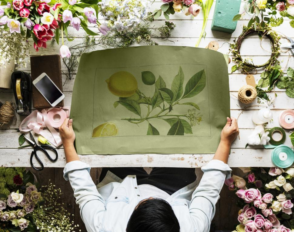 Download Free Stock Photo of Flat lay of a florist workspace with illustrated paper