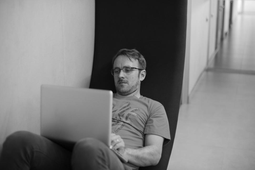 Download Free Stock HD Photo of A young man working on his laptop - black and white image Online