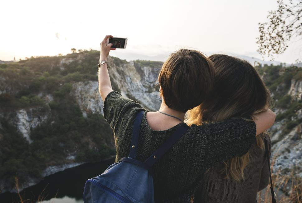 Download Free Stock HD Photo of Rear view of two young female hikers taking photo with mobile Online