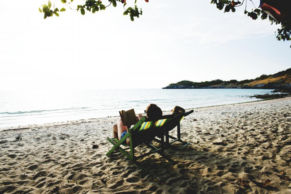 Download Free Stock Photo of A young woman reading book on the beach