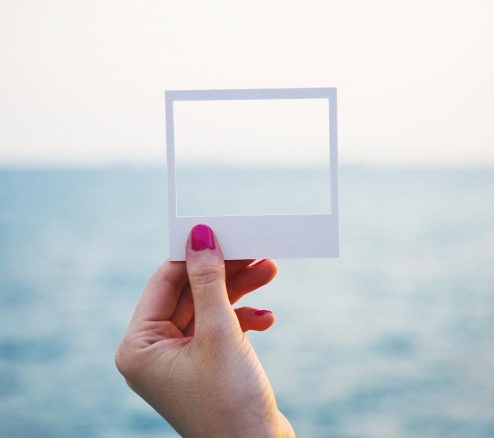 Download Free Stock Photo of A hand holding a square photo frame shaped paper cut out template