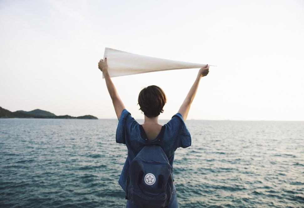Download Free Stock Photo of A young Caucasian woman holding white flag high at a seashore